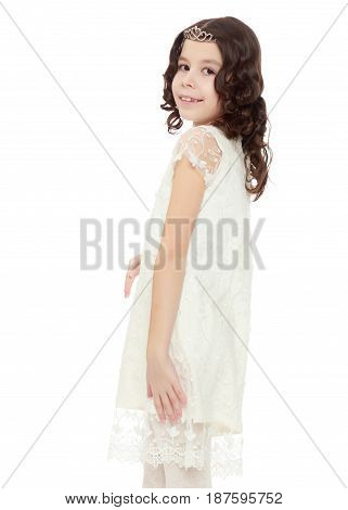 Beautiful little girl with long curly tails on the head, in which braided red ribbons . In a long white dress. The little girl turned sideways to the camera.Isolated on white background.