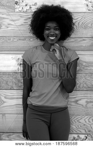 portrait of cute african american woman with afro hairstyle while  posing against old retro wooden background