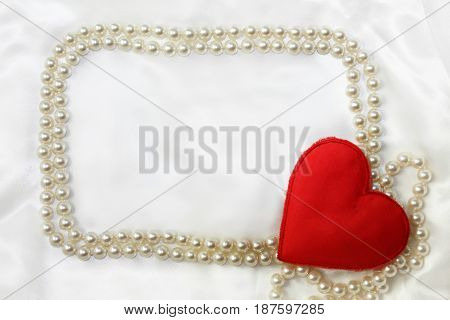 Silk canvas love background with red heart in the corner of beads frame