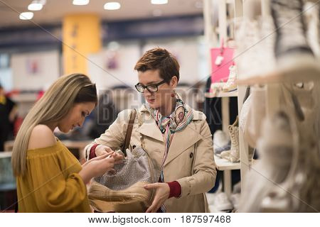 Two Girl-Friends On Shopping Walk On Shopping Centre With Bags And Choosing