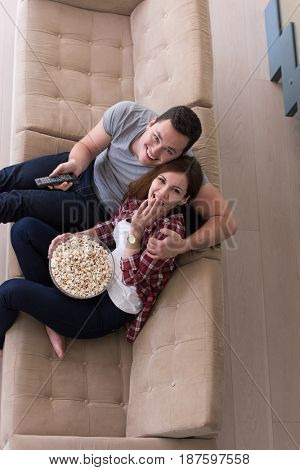 young handsome couple enjoying free time watching television with popcorn in their luxury home villa