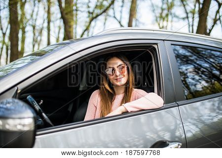 Pretty Young Woman Sitting In Car On Road