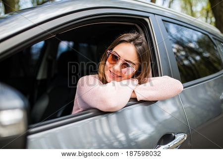 Attractive Young Female Looks Out The Car Window Waiting For A Trip And Smile