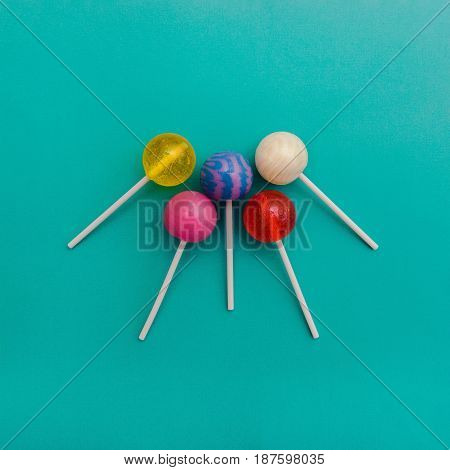Five colorful round lollipops are lying on a light blue background One-color and two-color candies