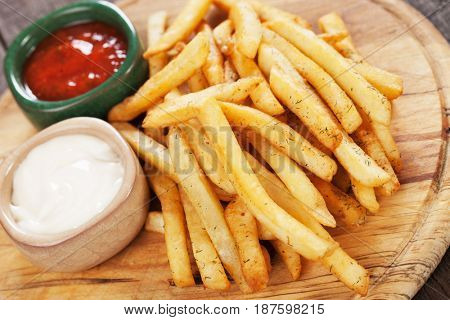 French fries with ketchup and mayonnaise on wooden board