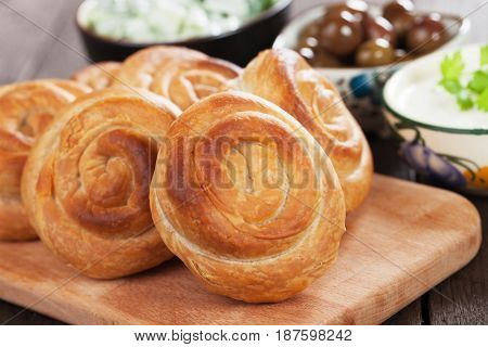 Phyllo pastry cheese pies with yogurt, salad and olives