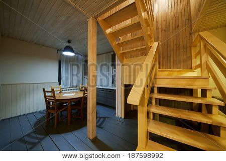 Interior of wooden house, kitchen with table and chairs, stairs to second floor.
