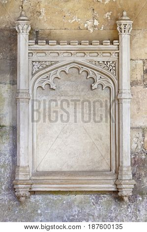 Architectural detail of an ornate stone frame. 13th century carved stonework, with decorative column, floral details, and an arched empty central area with space for text.