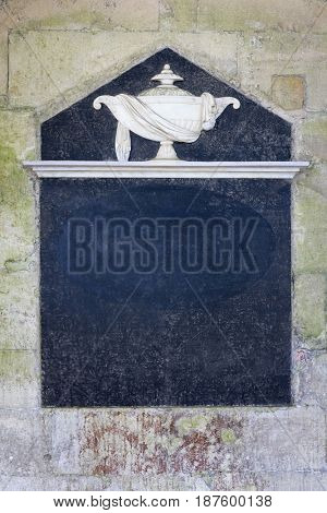 Architectural slate frame. 13th century carved stonework, with decorative urn with fabric detail, resting on a stone plinth, with a dark slate area and empty space for text.,