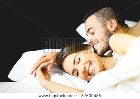 Young sexy couple of lovers lying on bed in their honeymoon - Young bearded man whispers and kissing in beautiful woman ear - Love and relationship concept of a couple together in bedroom