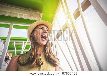 Happy woman enthusiast to be on ferris wheel while celebrating carnival festival - Young girl having fun in the cabin of the ferris wheel admiring the beautiful view in the top height poster