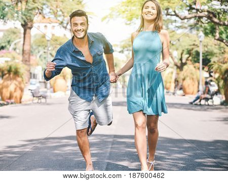 Front view of a casual couple holding hands while running across the street to catch a bus - Urban man and woman in a hurry - Vitality couple in summer vacation - Love and relationship concept