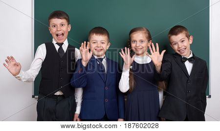 elementary school boy near blank chalkboard background, dressed in classic black suit, group pupil, education concept