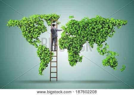 Businessman on ladder in green environment concept