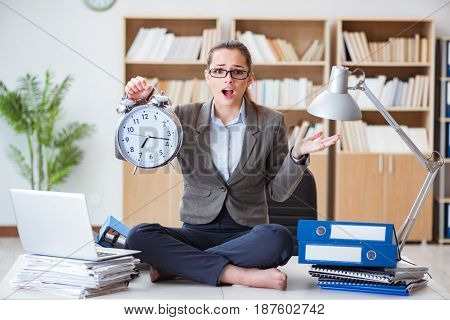 Businesswoman with alarm clock in office