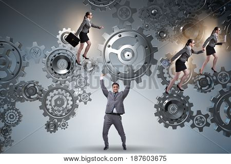 Businessman supporting gear in teamwork concept