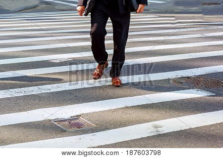 A businessman with a briefcase in a hurry to cross the road