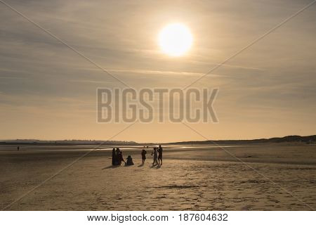 Silhouettes of a family on Camber Sands beach at low tide in spring  at sunset, East Sussex, England, U.K