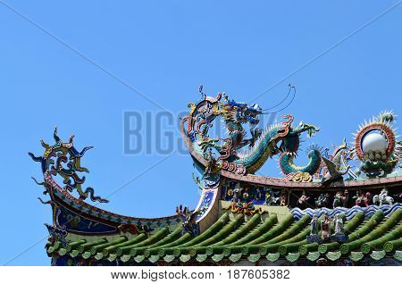 Dragon statue on Chinese temple roof against blue sky