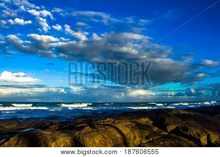 Sunset on a rocky beach with the sky with numerous white clouds