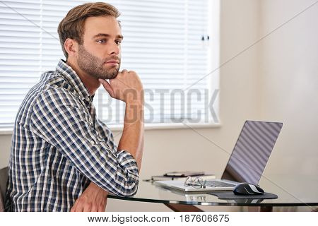 Young man resting his head on his hand while looking into the distance, day dreaming to procrastinate and get out of having to get back to work and study.
