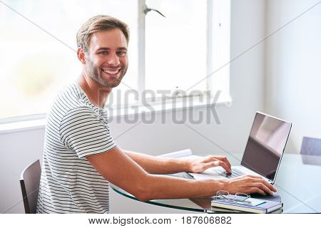 Good looking young male student smiling at camera while seated behind laptop over his shoulder on a bright and sunny morning in his plain white dorm room.