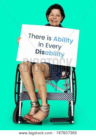 Senior adult woman on wheelchair holding motivation banner