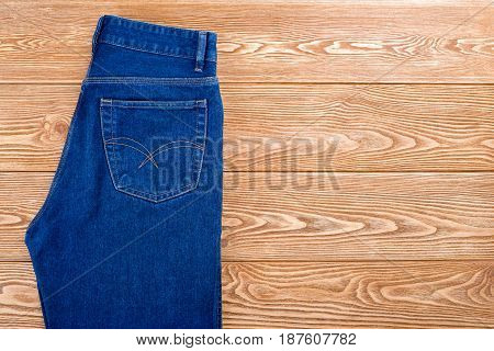 Folded blue jeans on a wooden background