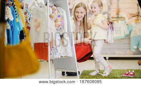 Shopping for kids - mother and daughter trying on new summer children's costume in front of a mirror