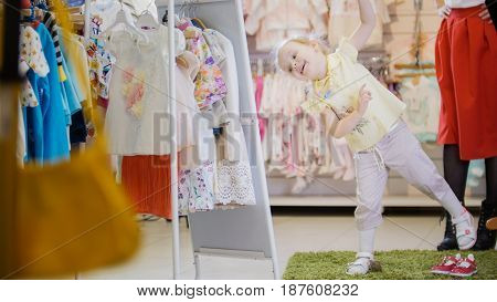 Little girl in a summer suit has fun in front of the mirror in the children's clothing store, shopping concept