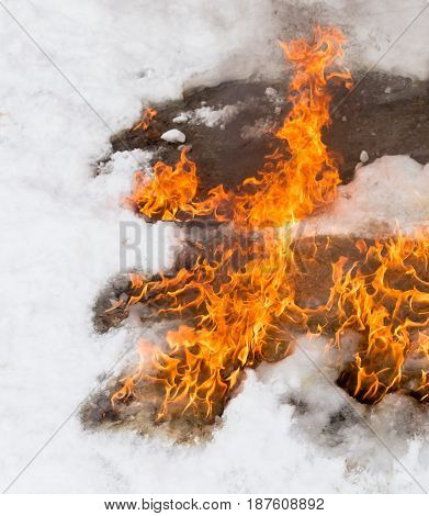 fiery flame on the white snow in winter .