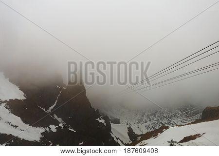 Dangerous downhill in fog. High cableway in fog. Foggy mountain landscape.