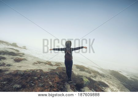 Tourist woman with hands to the side on mountain background. Freedom success concept.