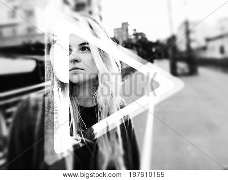 Young hipster woman listening music standing on the street