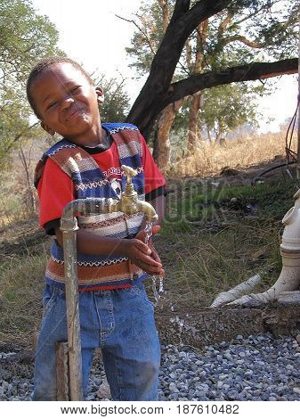 JUNE 6, 2005. CONGO, AFRICA.  CIRCA:  African boy using fresh water from a fountain in his village.