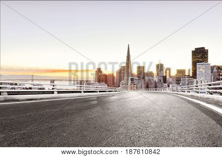 empty road with landmark buildings in san francisco at sunrise