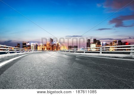 empty road with landmark buildings in hangzhou at twilight