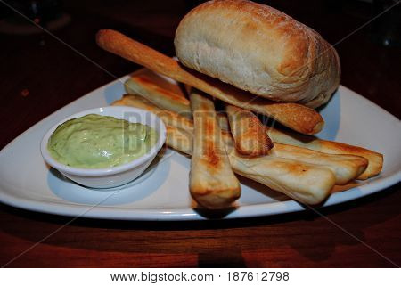 Stick bread, bread and avocado dip Freshly baked bread, stick bread and avocado dip in a small saucer