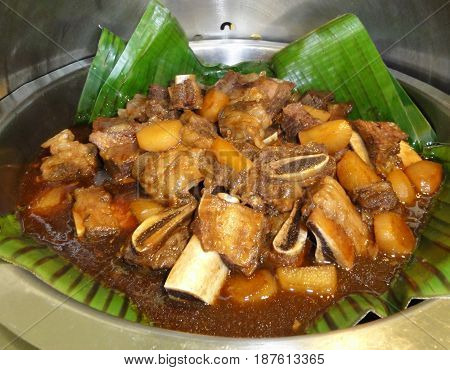 Beef meat stew Beef meat stewed with potatoes, pineapples, onions served in banana leaves in pot