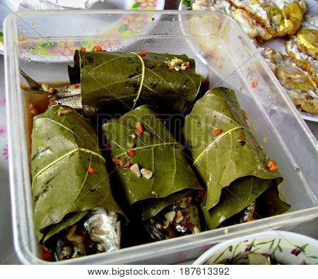 Fish paksiw wrapped in mango leaves- Filipino favorite Fish paksiw (inun-unan) is a favorite dish in the Visayas region of the Philippines where fish is wrapped in soft mango leaves and flavored with vinegar, ginger, and peppercorns then cooked in a clay