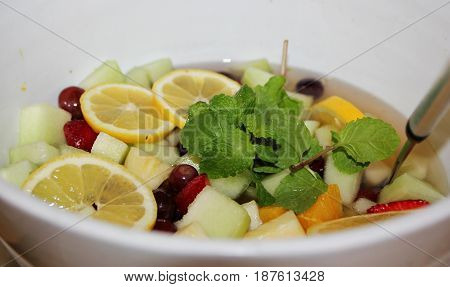 Fruit salad and herbs in a round white bowl An assortment of fruits including strawberries, dragonfruit, melon, lemon slices, blueberries and more in a round plate