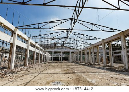 Demolition of an old building with roof only under blue sky