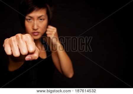 Asian woman kick boxing isolated on black.