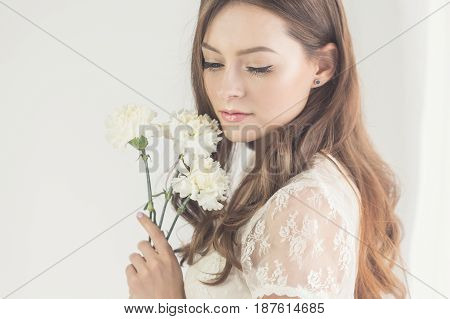 Sweet girl in a white dress is holding a bouquet of white flowers in her hands. She stands by the window with her eyes closed.