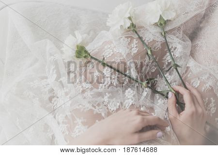 Flowers lie on the lap of a cute girl. She is wearing a white dress. Bride in anticipation of the ceremony. Man is unrecognizable.