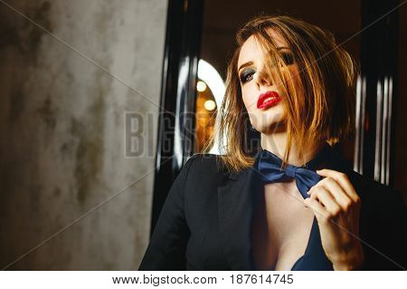 Young attractive girl in a jacket and bow tie. Femme fatale. Evening makeup smokey eye. She straightens her tie. Passion and desire.