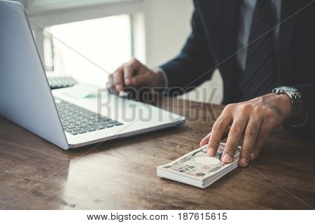 Businessman giving money on the table Japanese yen banknotes - loan financial bribery and corruption concepts
