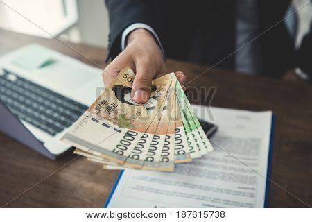 Businessman giving money South Korean won bills at working desk