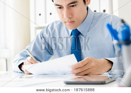 Young businessman seriously concentrating on paperwork in the office