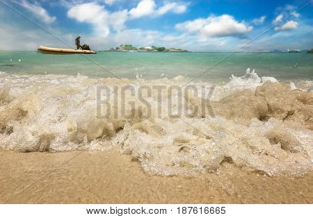 Waves in the ocean and sand on the beach fisher man background